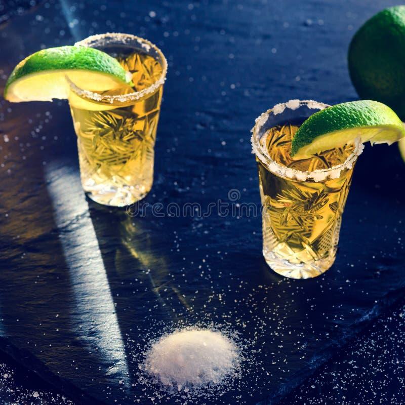 Den guld- mexicanska tequilaen med limefrukt och saltar på den mörka tabellen, tonad ima arkivbild