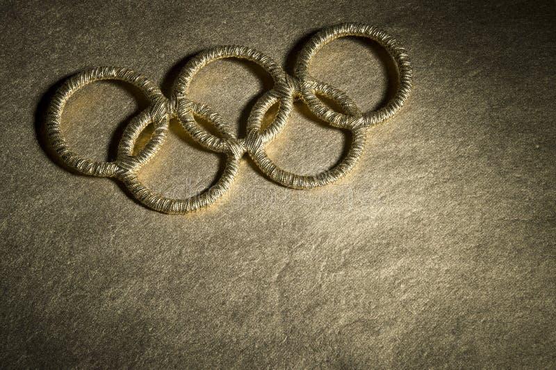 Den guld- OS:en ringer symbol under strålkastare royaltyfri fotografi