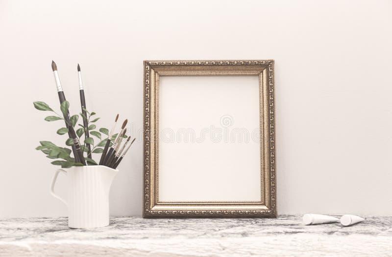 Den guld- ramåtlöjet upp på den vita tabellen och konstborstarna royaltyfria bilder