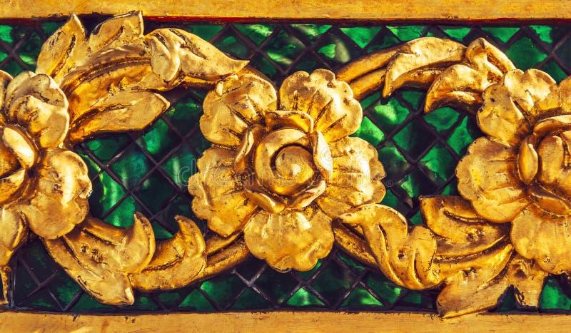 Den guld- stuckaturdesignen av infödd thai stil på väggen arkivfoton