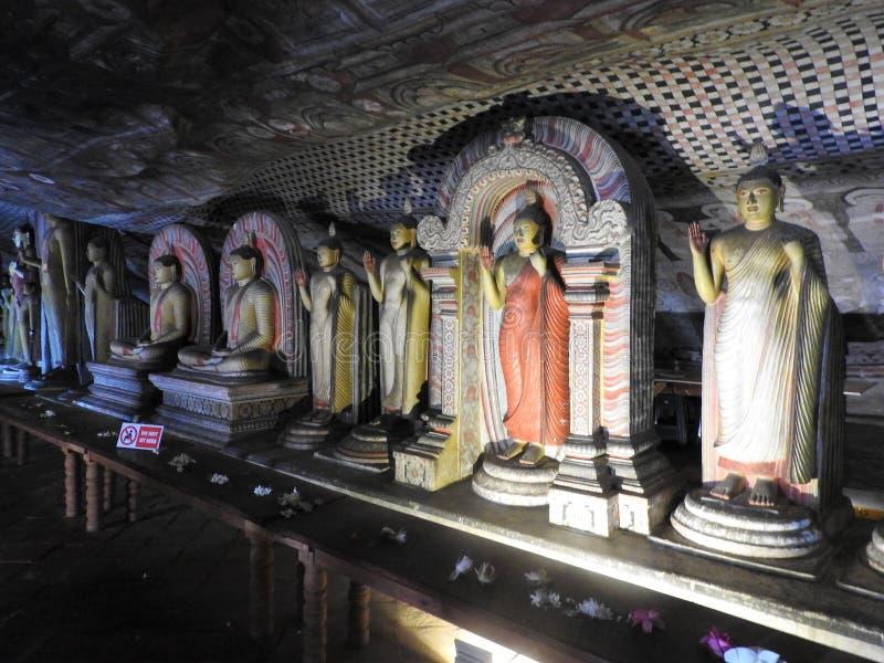 Den guld- templet av Dambulla ?r v?rldsarvet och har en slutsumma av en slutsumma av 153 Buddhastatyer, tre statyer av srilankesi arkivbilder