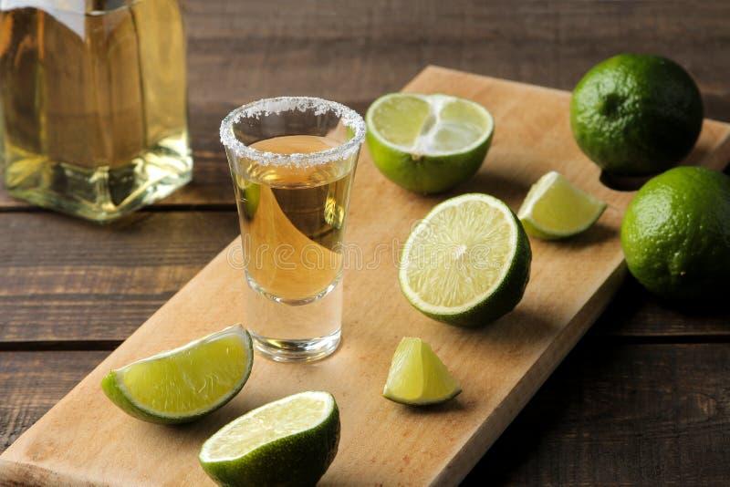 Den guld- tequilaen i ett exponeringsglas med saltar och kalkar på en brun trätabell alkoholiserada drycker royaltyfri bild
