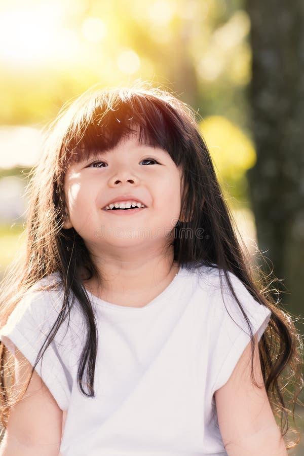 Den gulliga asiatet behandla som ett barn att le i trädgård arkivbild