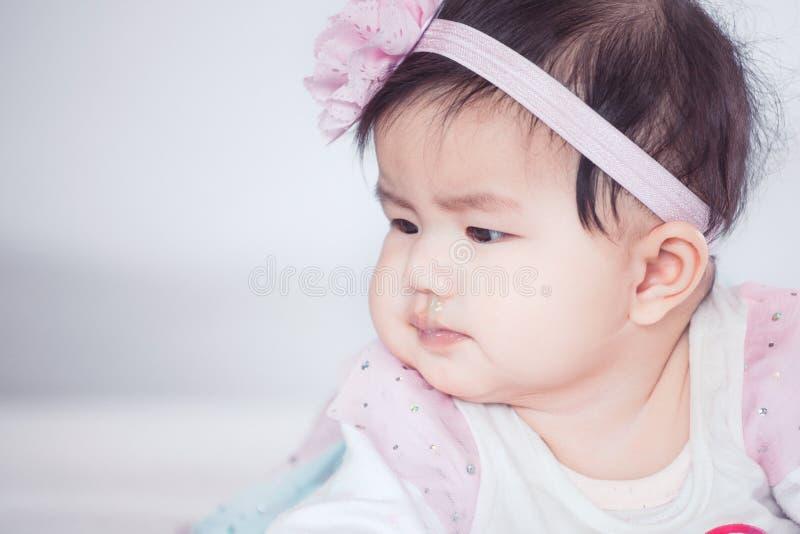 Den gulliga asiatet behandla som ett barn flickan som ligger på hennes mage på säng royaltyfria foton