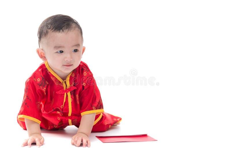 Den gulliga asiatet behandla som ett barn i dräkt för traditionell kines med det röda facket, Iso arkivfoto