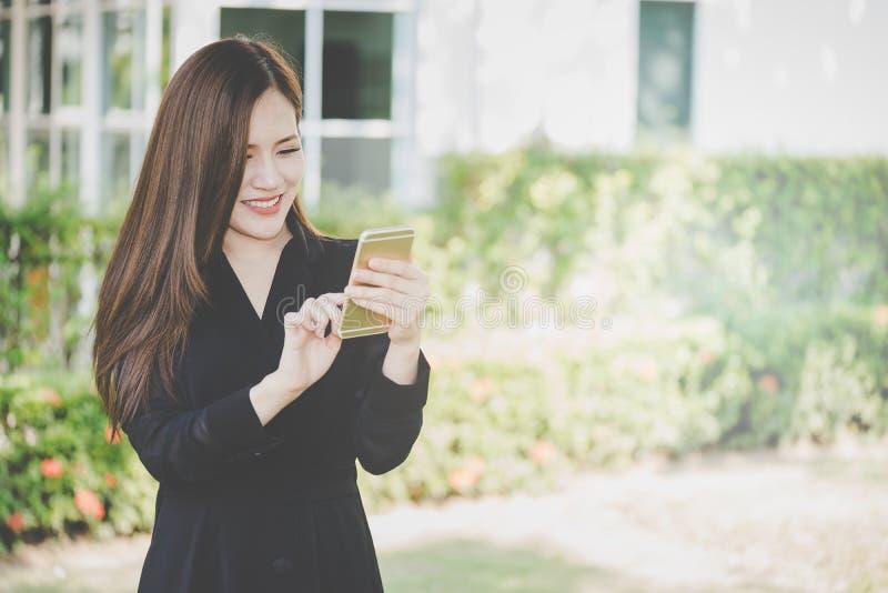 Den gulliga asiatiska flickan som använder mobiltelefonen parkerar in royaltyfri bild