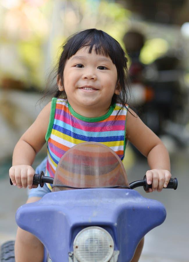 Den gulliga asiatiska flickan tycker om att spela leksakbilen royaltyfri bild