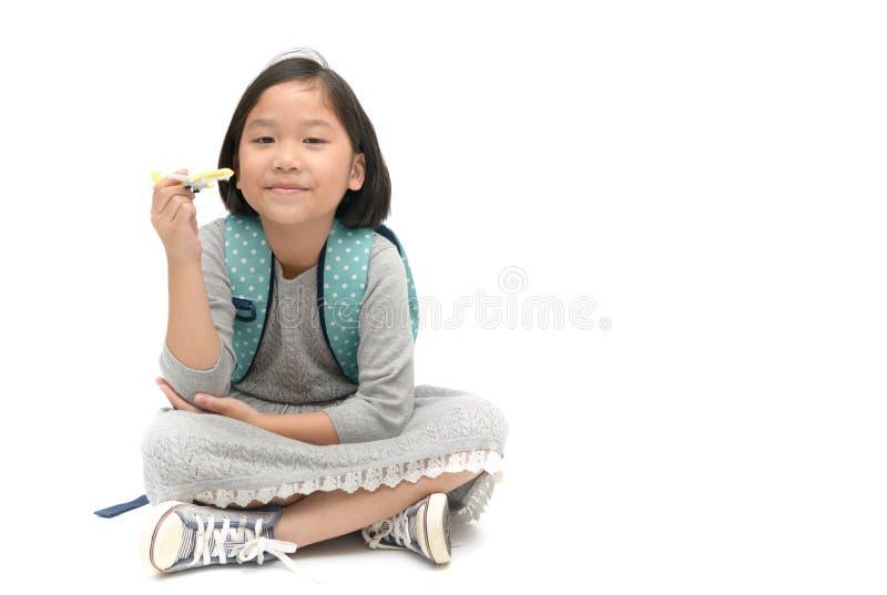 Den gulliga asiatiska flickastudenten med ryggsäcken sitter och rymma den plana leksaken royaltyfria bilder