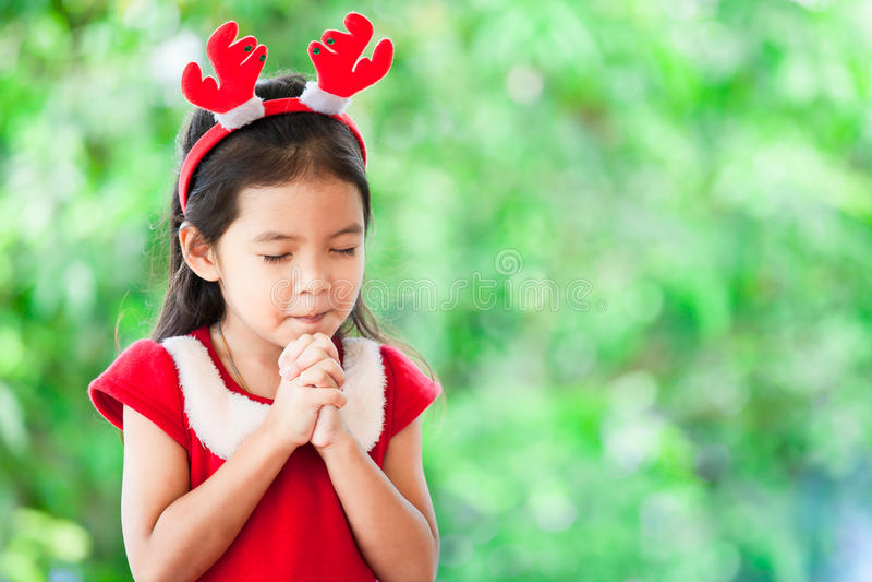 Den gulliga asiatiska lilla flickan i julklänning stängde henne ögon arkivfoto