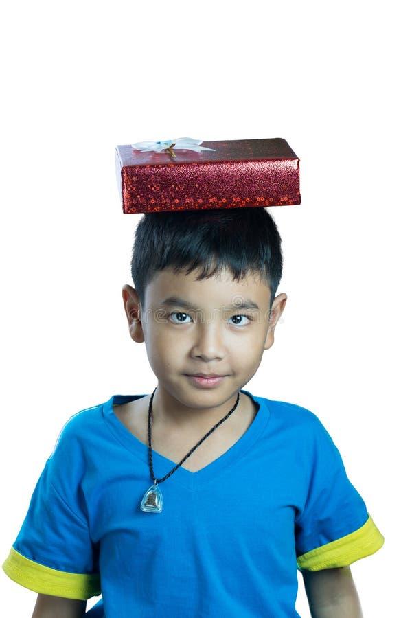 Den gulliga asiatiska ungen satte den närvarande asken på hans huvud arkivfoto