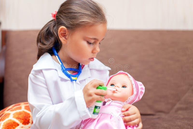 Den gulliga barnflickan som spelar doktorn med, behandla som ett barn - dockaleksaken arkivfoto