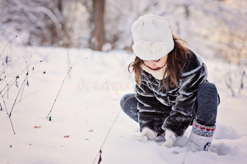Den gulliga barnflickan spelar med den insnöade vinterskogen royaltyfria bilder
