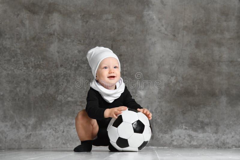 Den gulliga bilden av behandla som ett barn rymma en fotbollboll arkivfoton