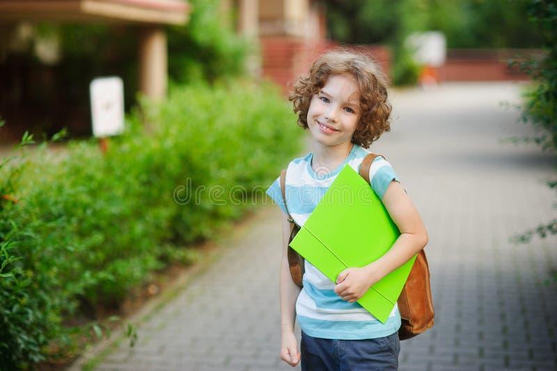 Den gulliga blåögda skolpojken med ett leende ser i kameran royaltyfri fotografi