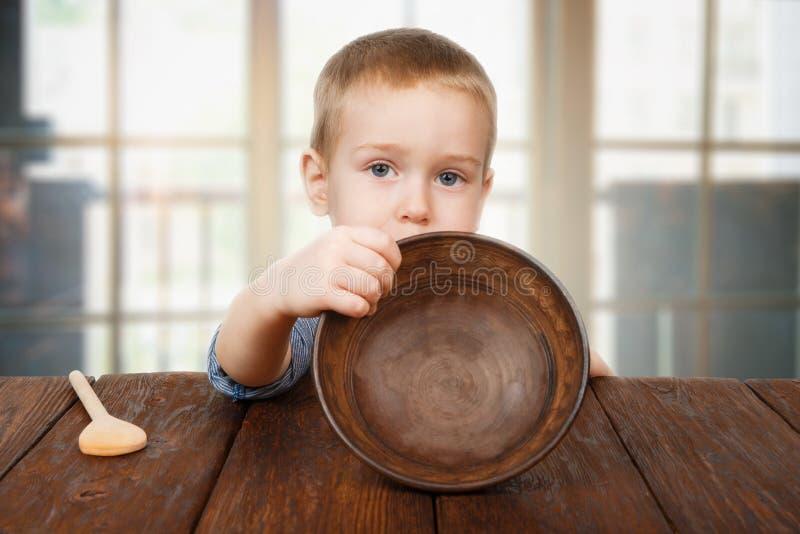 Den gulliga blonda pojken visar den tomma plattan, hungerbegrepp royaltyfria foton