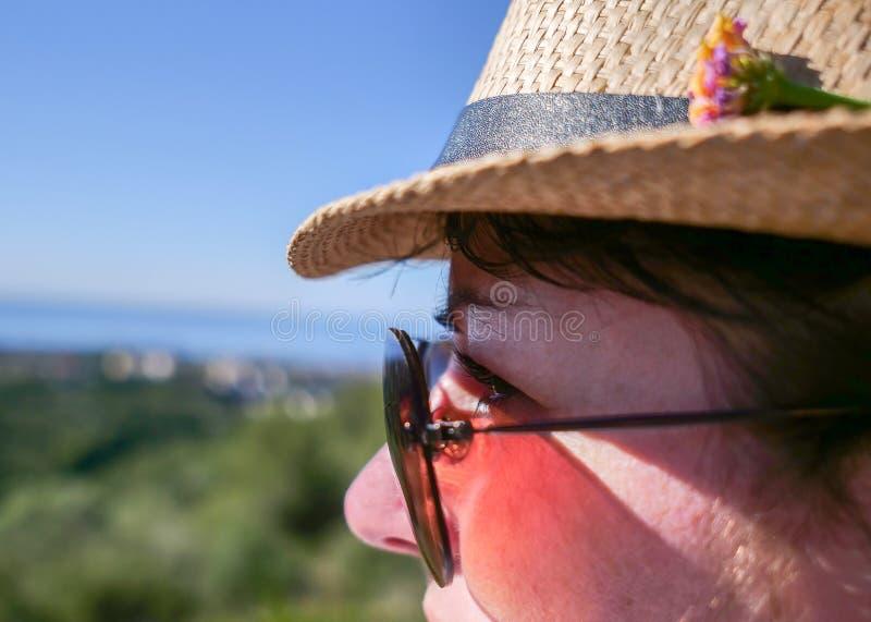 Den gulliga brunettflickan i solglasögon och en hatt med en blomma ser bort, närbilden arkivfoton