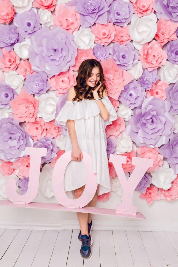 Den gulliga brunettflickan står och rymmer träordet GLÄDJE som brett ler Hon har lockigt hår och bär den vita klänningen av royaltyfria bilder