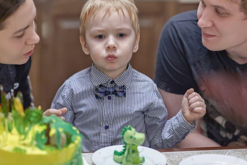 Den gulliga caucasian blonda pojken äter raringar från födelsedagkakan som sitter mellan föräldrarna royaltyfria bilder