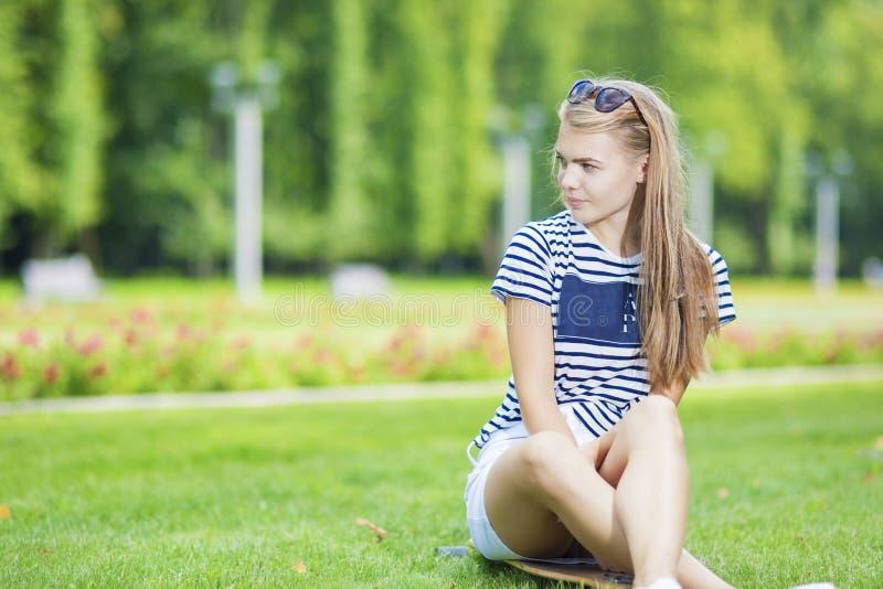 Den gulliga Caucasian blonda tonårs- flickan med Longboard i grön sommar parkerar arkivbilder