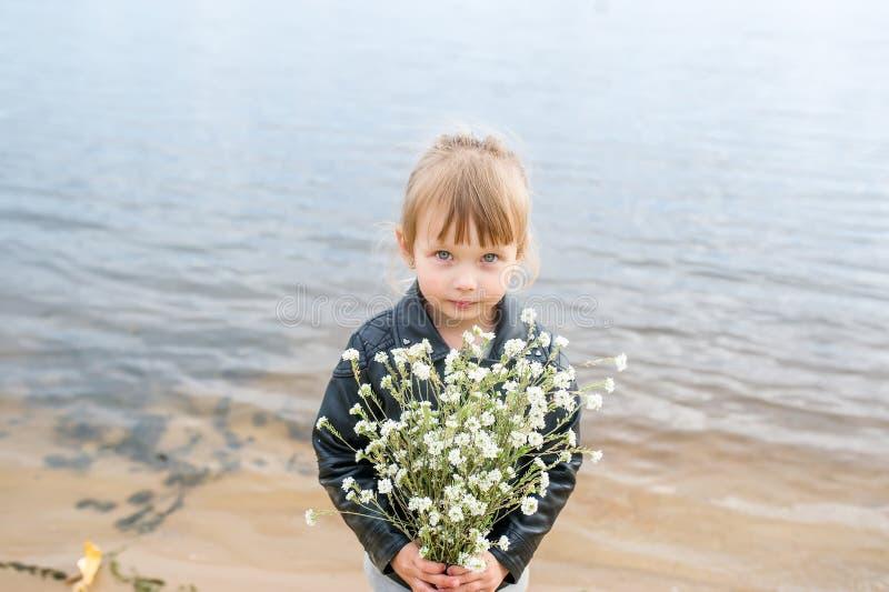 Den gulliga caucasian flickan i vildblommor för omslagshåll a bredvid en sjö i parkerar arkivfoton