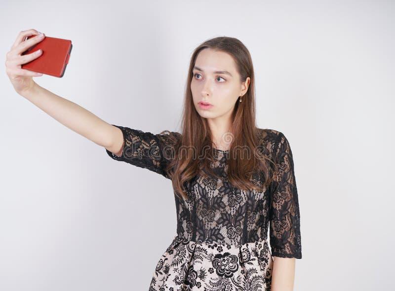 Den gulliga caucasian vänliga flickan står med en mobiltelefon i hennes hand och tar en lycklig emotionell selfie på en vit ba royaltyfri fotografi