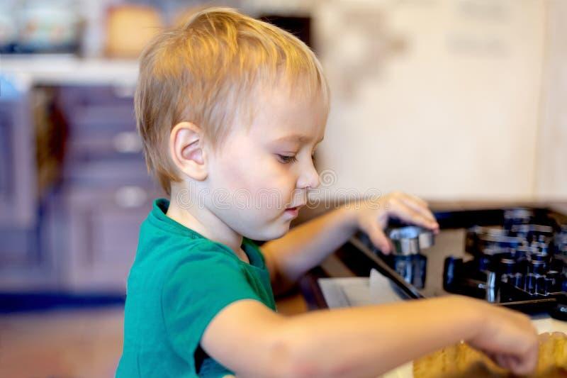 Den gulliga caucasianen behandla som ett barn pojkehjälp i kök som gör coockies Tillfällig livsstil i hemmiljön, nätt barn bara fotografering för bildbyråer