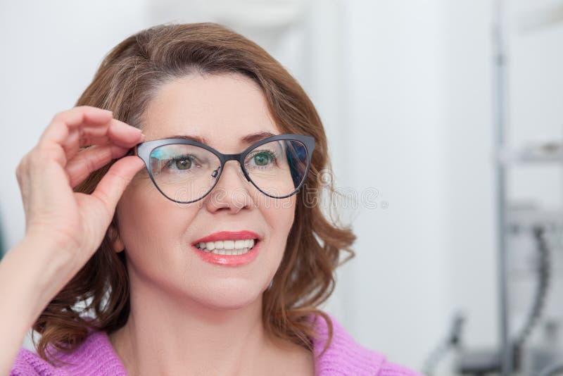 Den gulliga damen försöker på eyewearen i klinik arkivbilder
