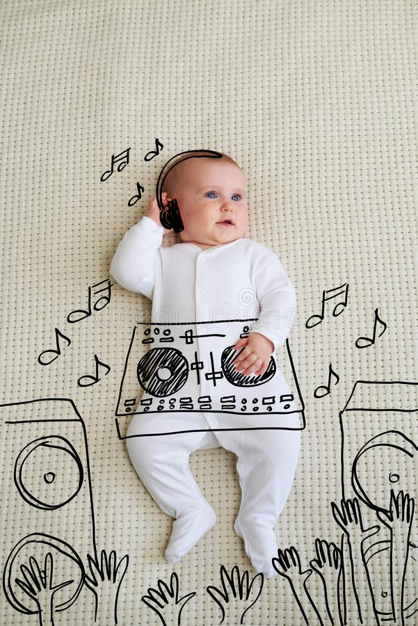 Den gulliga discjockeyn behandla som ett barn bärande hörlurar för flickan som spelar musik på blandaren fotografering för bildbyråer