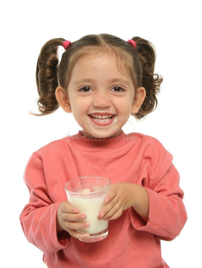 den gulliga dricka flickan mjölkar little arkivbild