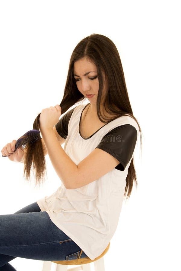 Den gulliga etniska tonåriga flickan frustrerade att borsta hennes hår arkivfoto
