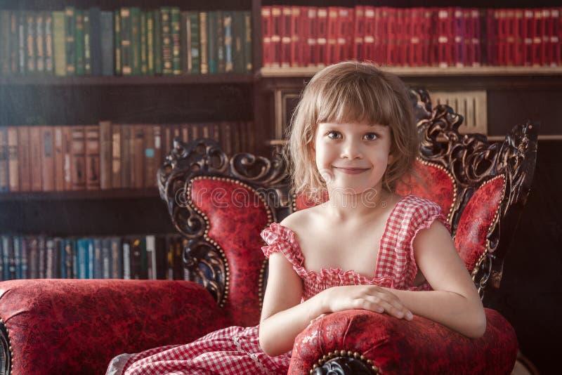 Den gulliga femåriga flickan sitter på en röd fåtölj royaltyfri fotografi