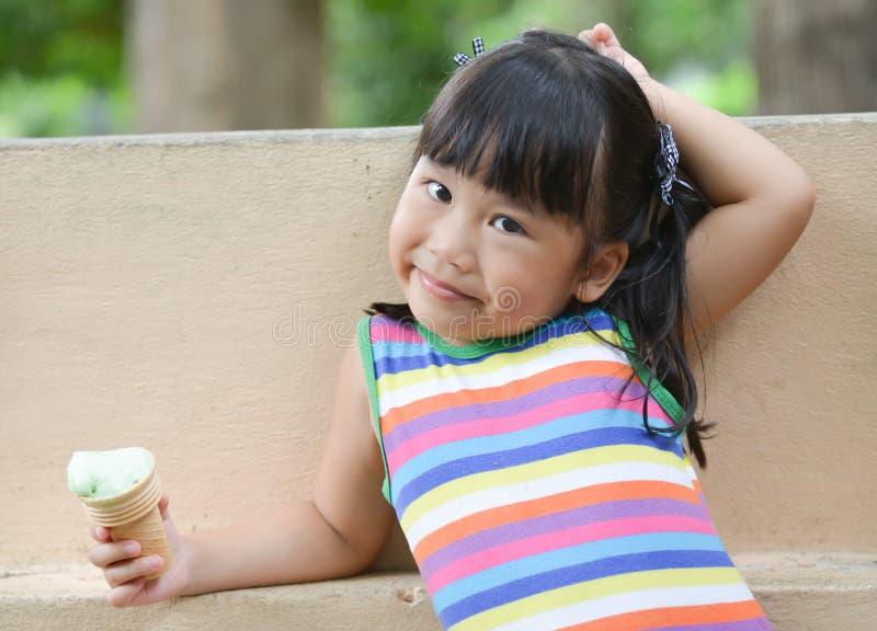 Den gulliga flickaasiatet gillar att äta glass royaltyfria bilder