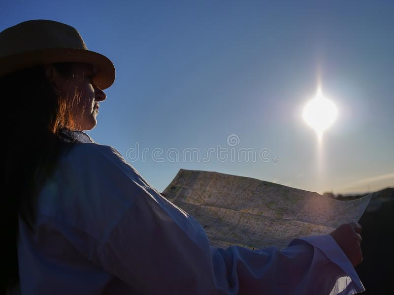 Den gulliga flickahandelsresanden i en hatt undersöker en översikt av området mot stigningssolen, copyspace arkivfoton