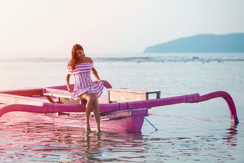 Den gulliga flickan doppade hennes ben i vattnet som sitter på fartyget arkivbilder