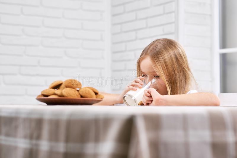 Den gulliga flickan dricker mjölkar nära plattan med kakor arkivbild