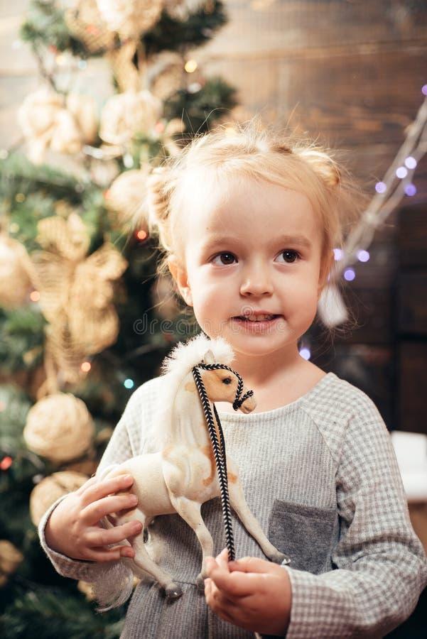 Den gulliga flickan för det lilla barnet dekorerar julgranen inomhus Öppningsgåvor på jul och nytt år Gulligt litet royaltyfri bild