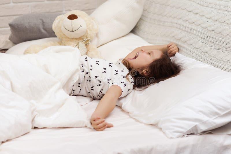 Den gulliga flickan f?r det lilla barnet vaknar upp fr?n s?mn arkivbilder