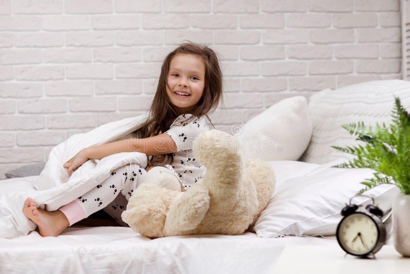 Den gulliga flickan f?r det lilla barnet vaknar upp fr?n s?mn arkivfoton