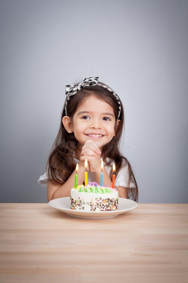 Den gulliga flickan gör en önska på födelsedag lycklig bakgrundsfödelsedag royaltyfri bild
