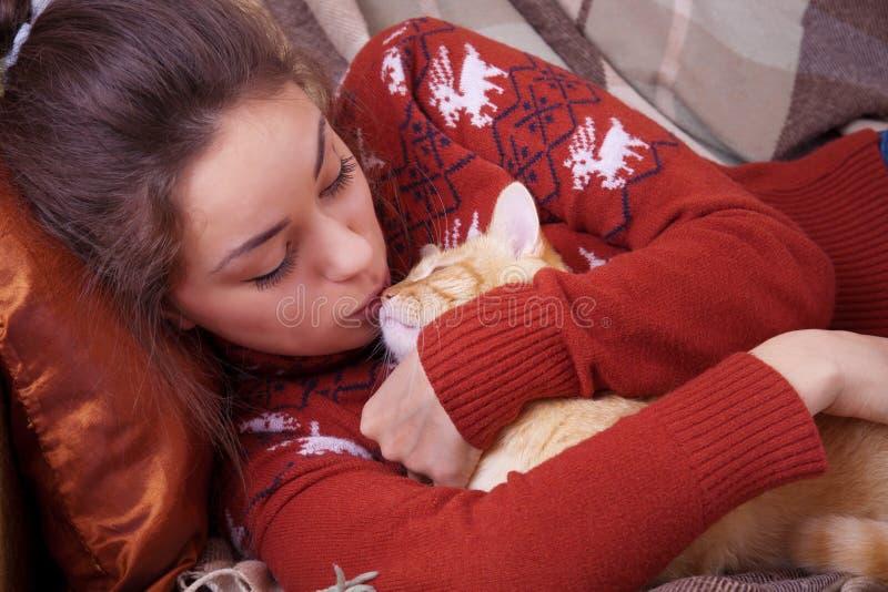 Den gulliga flickan kysser en röd katt arkivfoton