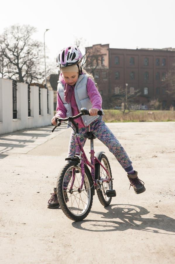 Den gulliga flickan lär att rida en cykel royaltyfria bilder