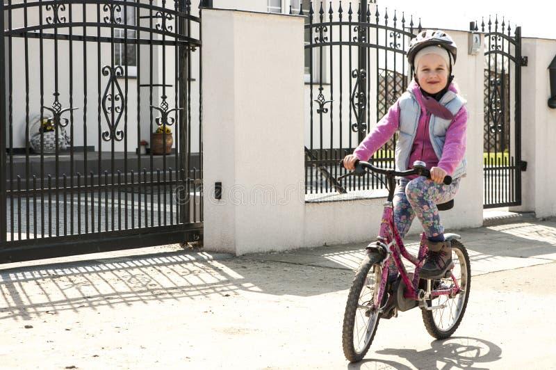 Den gulliga flickan lär att rida en cykel royaltyfri fotografi