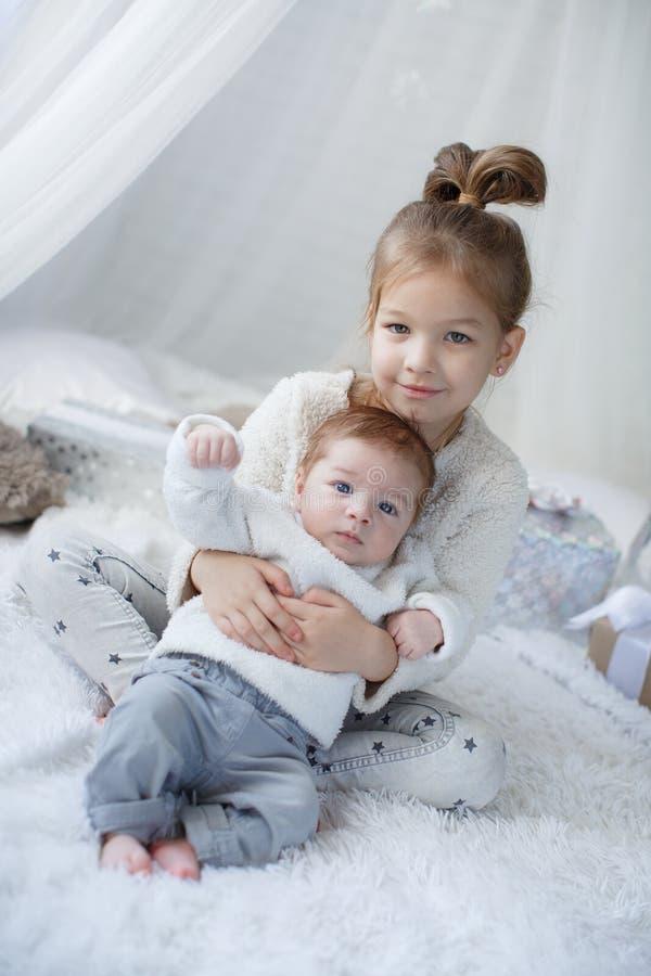 Den gulliga flickan med ett nyfött behandla som ett barn brodern som tillsammans kopplar av på en vit säng royaltyfri fotografi