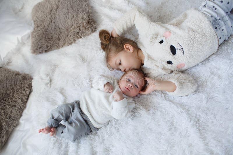 Den gulliga flickan med ett nyfött behandla som ett barn brodern som tillsammans kopplar av på en vit säng arkivfoto