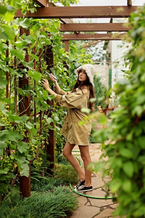 Den gulliga flickan med långt hår gör klipp med stor trädgårds- sax royaltyfri fotografi