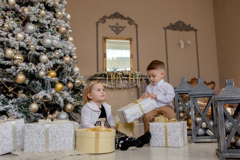 Den gulliga flickan och pojken som öppnar Xmas, framlägger Barn under julgranen med gåvaaskar Dekorerad vardagsrum med traditione royaltyfria bilder