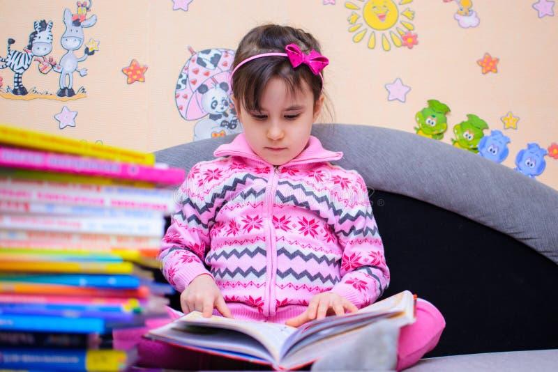 Den gulliga flickan på bakgrunden av henne leker med en bok arkivbild