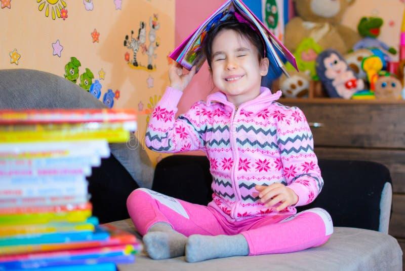Den gulliga flickan på bakgrunden av henne leker med en bok fotografering för bildbyråer