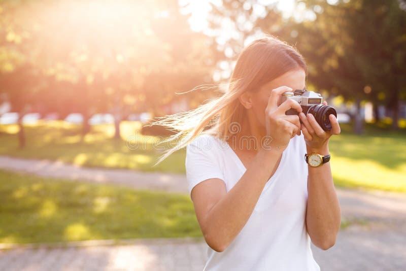 Den gulliga flickan på solig dag i parkering som tar foto med motsvarighet, kom arkivfoto