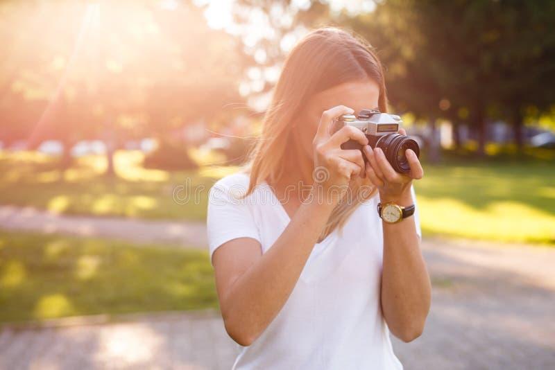 Den gulliga flickan på solig dag i parkering som tar foto med motsvarighet, kom royaltyfri bild